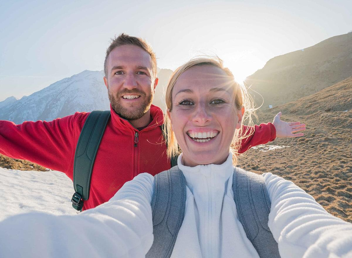 Happy couple in the mountains takes a selfie
